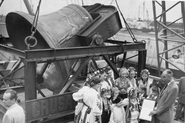 A group of former displaced persons helps load the Freedom Bell aboard a Navy transport vessel in Brooklyn, N.Y., on Oct. 9, 1950. One of the children, Eva Zandler, 8, originally from Poland, presents a scroll — to be enshrined in the Freedom Bell's tower in Berlin — to Frederick Osborn, the New York City chairman of the Crusade for Freedom.