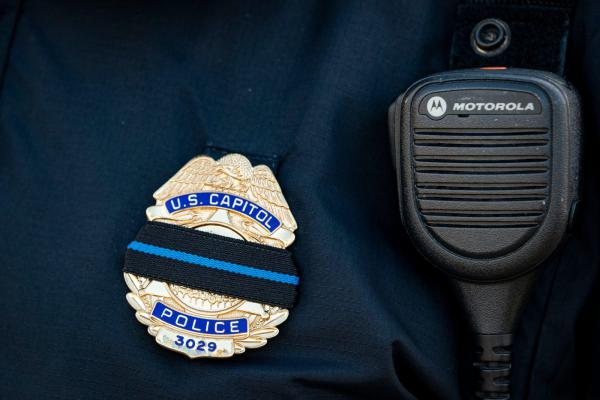 A U.S. Capitol Police officer wears a mourning band over his badge following a police procession of the hearse carrying the casket of Brian Sicknick, U.S. Capitol Police Officer who died from injuries following the U.S. Capitol building siege in Washington, DC.