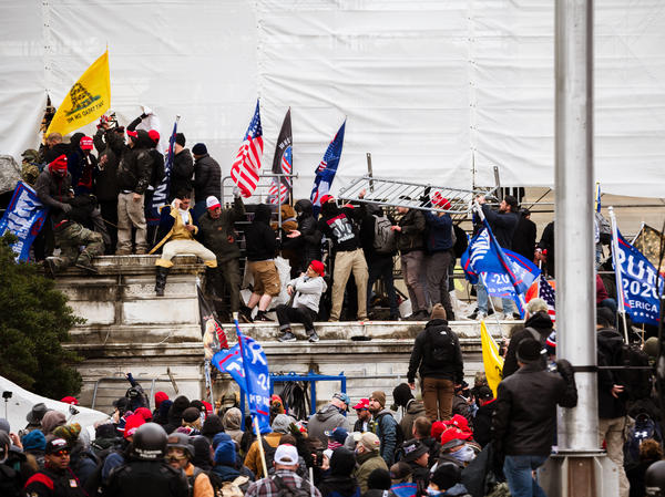 Pro-Trump extremists climb the walls of the U.S. Capitol on Jan. 6. The pro-Trump mob broke windows of the Capitol and clashed with police officers. Now there's debate about whether federal charges of seditious conspiracy should be used against some of the rioters.