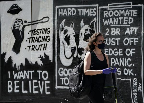 A woman with a face mask walks by a mural by contemporary artist Stephen Powers, also known as ESPO in New York.