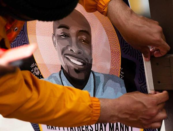 Community members gathered in June for a celebration of life for Manuel Ellis, who was killed by Tacoma police in March. In this photo, one of the attendees hangs a flyer that says 'Happy Father's Day Manny'