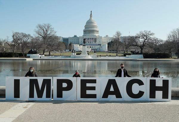 People gather at the base of the U.S. Capitol with large IMPEACH and REMOVE letters in Washington, DC.