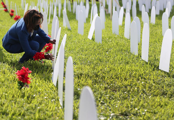 Mary Estime-Irvin, a councilwoman in North Miami, Fla., writes the name of a friend lost to COVID-19 on a symbolic tombstone that is part of a pandemic memorial at Griffing Park in North Miami in October.