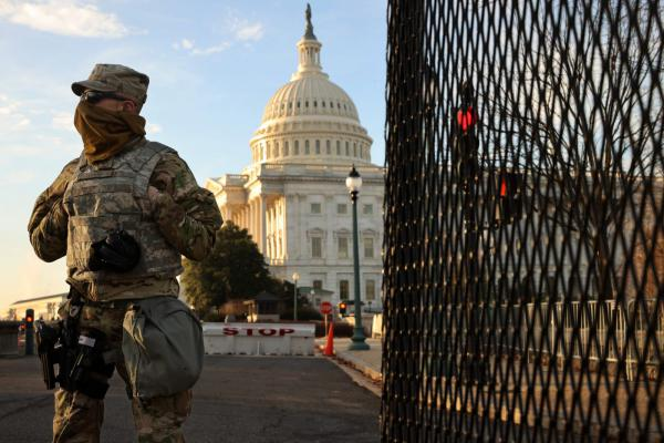 A member of the New York National Guard stands at a gate outside the U.S. Capitol the day after the House of Representatives voted to impeach President Donald Trump for the second time in Washington, DC.