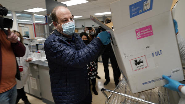 Gov. Jared Polis helps put Colorado's first shipment of COVID-19 vaccine in a freezer at a state health department laboratory last week.