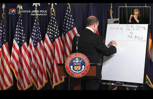 Gov. Jared Polis does math during a news conference to estimate how many vaccines the state will receive in the coming weeks.