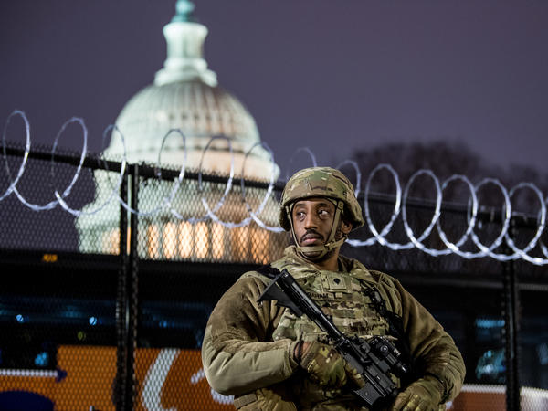 A member of the Virginia National Guard stands outside the razor wire fencing surrounding the U.S. Capitol on Friday. Up to 25,000 troops are expected by Inauguration Day.