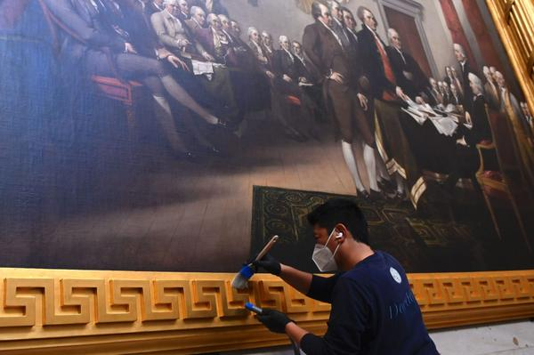 A preservationist cleans the frame around a painting inside the US Capitol Rotunda after a insurrectionist mob breached the Capitol on Jan. 6.