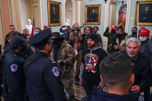 A man wearing a QAnon sweatshirt stands off against US Capitol police officers as they try to stop pro-Trump insurrectionists from entering the U.S. Capitol in Washington, D.C.