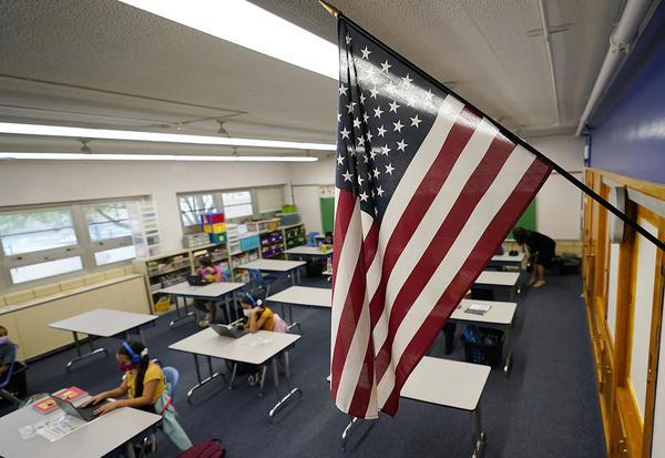 A U.S. flag hangs in a classroom as students work on laptops in Newlon Elementary School in Denver, Colorado. (David Zalubowski/AP)