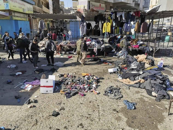 People and security forces gather at the site of deadly bomb attacks Thursday in a Baghdad market. The rare suicide bombings killed and wounded dozens of civilians.