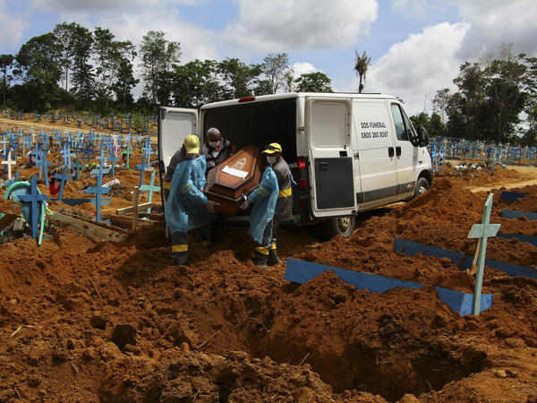 Cemetery workers carry the remains of 89-year-old Abilio Ribeiro, who died of the new coronavirus, for burial at the Nossa Senhora Aparecida cemetery in Manaus, Amazonas state, Brazil, on Jan. 6. The day before, Manaus declared a 180-day state of emergency due to a surge of new cases of the coronavirus.