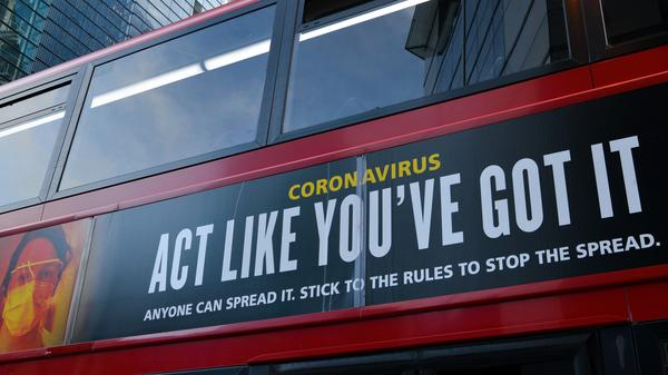 "Moderna will test new COVID-19 vaccine booster doses, saying that while its vaccine should protect against variants found in the U.K. and South Africa, it isn't as effective against the South African strain. Here, a bus in London carries a sign telling people, ""Act Like You've Got It"" — to prevent the coronavirus from spreading."