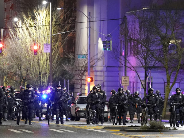 Police and other law enforcement officials stand in a line as protesters approach Sunday in the street in front of the City-County Building in Tacoma, Wash.