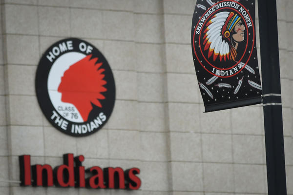 A light pole at the Shawnee Mission North gymnasium parking lot holds a display banner of the school's mascot, while the gymnasium bears the  likeness of a Native American wearing a headdress.