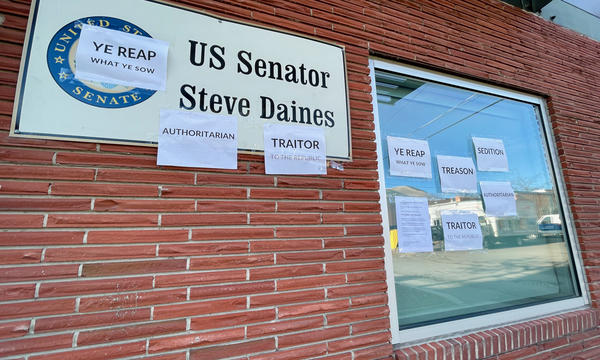 """While a mob stormed the Capitol on January 6, someone protested Republican Montana Sen. Steve Daines's role in inciting the insurrection by taping signs to his Missoula office with the words """"sedition"""" and """"authoritarian."""""""