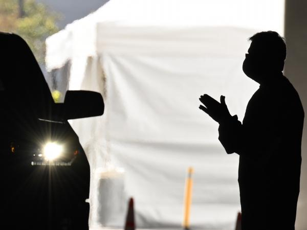 A health care worker instructs people arriving in their cars to be tested for COVID-19 at a new coronavirus drive through testing site in Redondo Beach, Calif.