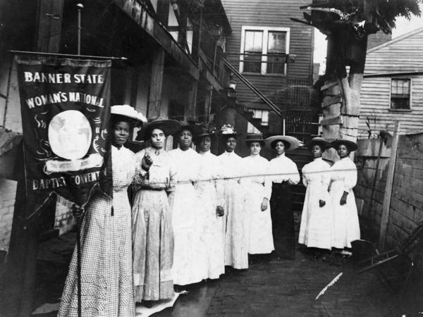 """Nannie Helen Burroughs holds a banner reading, """"Banner State Woman's National Baptist Convention"""" as she stands with other African American women, photographed between 1905 and 1915. Burroughs was an educator and activist who advocated for greater civil rights for African Americans and women."""