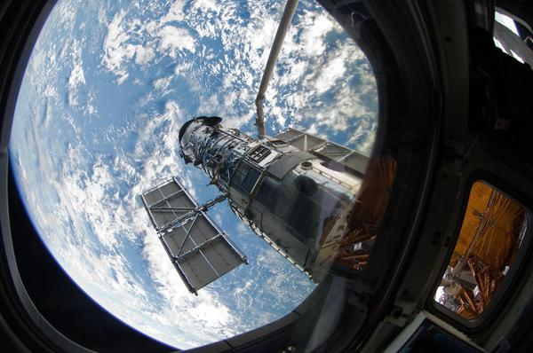An STS-125 crew member onboard the space shuttle Atlantis snaps a still photo of the Hubble Space Telescope following grapple of the giant observatory by the shuttle.