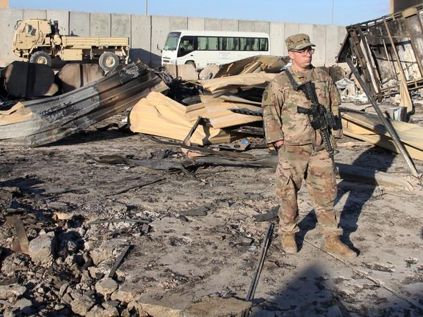 A U.S. soldier stands at a spot struck by Iranian missiles in January at Ain al-Asad air base in Iraq's Anbar province. The attack was in retaliation for the U.S. drone strike that killed Iranian Gen. Qassem Soleimani. The U.S. is drawing down 2,500 troops in Iraq and Afghanistan.