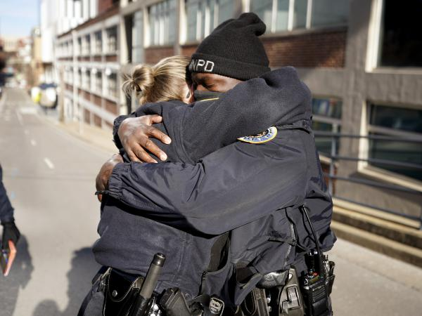 Nashville, Tenn., police officers Brenna Hosey and James Wells embrace after speaking at a news conference on Sunday. Hosey and Wells are part of a group of officers credited with evacuating people before the explosion that occurred in downtown Nashville early Christmas morning.