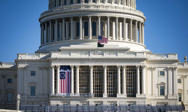 The American flag flies at half-staff on the west front of the U.S. Capitol after the Jan. 6 insurrection.