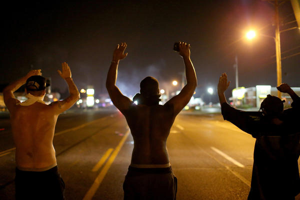"""Demonstrators raise their arms and chant, """"Hands up, don't shoot,"""" in August 2014 as they protest the shooting death of Michael Brown in Ferguson, Mo."""