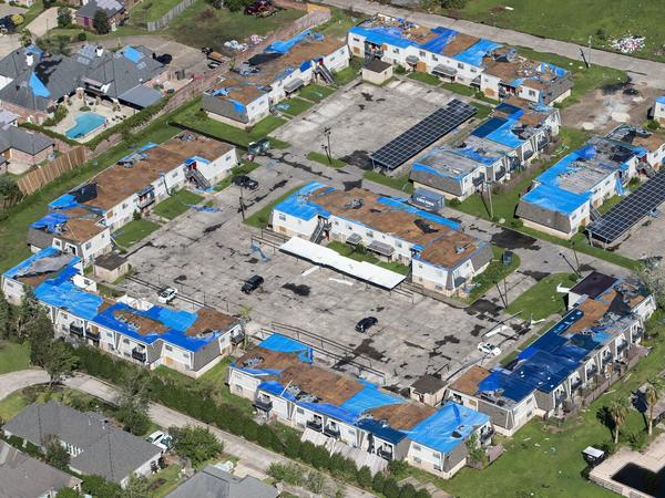 Blue tarps cover houses with damaged roofs in Lake Charles, La., after Hurricane Delta hit the city in October 2020.