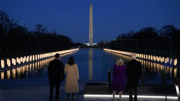 """President-elect Joe Biden; his wife, Jill Biden; Vice President-elect Kamala Harris; and her husband, Doug Emhoff, listen as Yolanda Adams sings """"Hallelujah"""" during a COVID-19 memorial, with lights placed around the Lincoln Memorial's reflecting pool, on Tuesday."""
