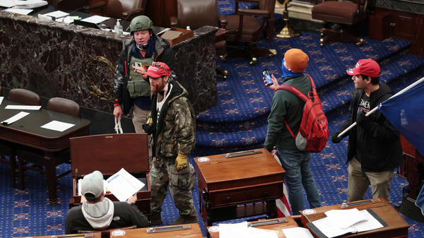 "Larry Rendall Brock Jr., an Air Force veteran, is seen inside the Senate Chamber wearing a military-style helmet and tactical vest during the rioting at the U.S. Capitol. Federal prosecutors have alleged that before the attack, Brock posted on Facebook about an impending ""Second Civil War."""