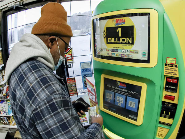 A patron, who did not want to give his name, uses the lottery ticket vending kiosk at a Smoker Friendly store to purchase tickets for the Mega Millions lottery drawing Friday in Cranberry Township, Pa.