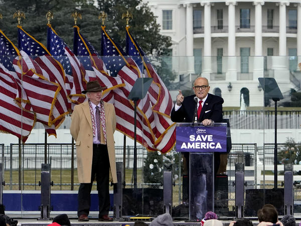 Rudy Giuliani, seen here on Jan. 6 with Chapman University law professor John Eastman, speaks in Washington at a rally in support of former President Donald Trump. Dominion Voting Systems, a frequent target of Giuliani, is suing him for defamation.