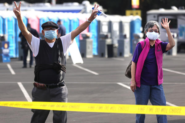 Southern Californians celebrate at a mass vaccination site in Disneyland's parking lot in January. CDC head Dr. Rochelle Walensky cautions that for strongest immunity, recipients get both doses of the Pfizer or of the Moderna vaccine.