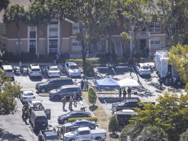 The FBI says Special Agent Daniel Alfin and Special Agent Laura Schwartzenberger died during a raid that was part of an investigation into violent crimes against children. Here, law enforcement officers investigate the scene of the raid — an apartment complex in Sunrise, Fla.