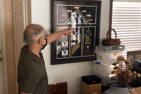 Veteran Marc Session points to some of his Navy mementos on display in his Chula Vista, California home.