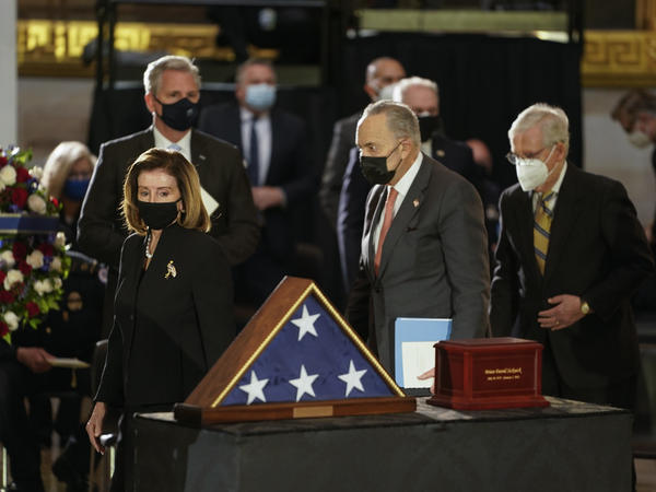 Speaker of the House Nancy Pelosi, left, and Senate Majority Leader Chuck Schumer, center, walk past the remains of U.S. Capitol Police Officer Brian Sicknick as he lies in honor in the Rotunda of the Capitol on Wednesday.