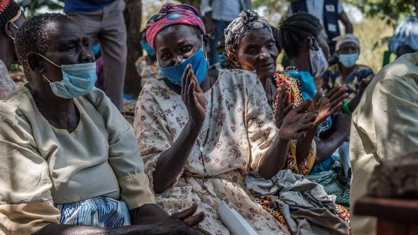 Women in Lukodi, Uganda, celebrate after hearing on a radio that the International Criminal Court in The Hague, Netherlands, found Dominic Ongwen guilty of war crimes, including a massacre in their village back in 2004.