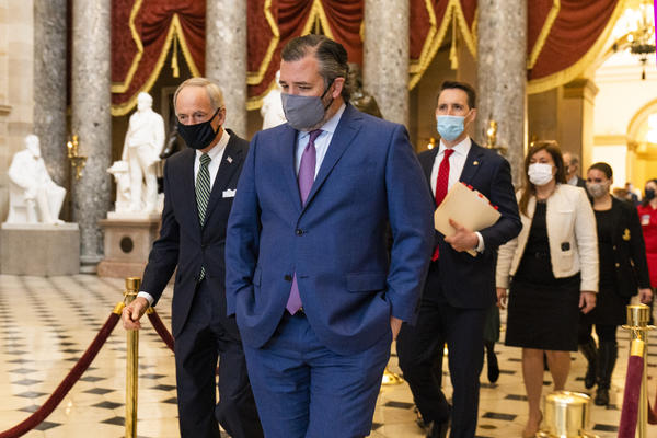 Sen. Ted Cruz, R-Texas, front, followed by Sen. Josh Hawley, R-Mo., walk from the House Chamber following a Senate procession carrying boxes holding Electoral College votes to the House Chamber for a joint session to confirm the Electoral College votes, Wednesday, Jan. 6, 2021, in Washington.