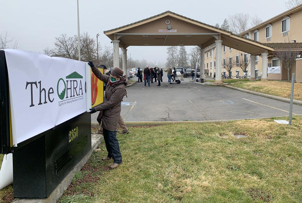 OHRA Director of Administration Pam Lott rolls up a banner covering the former Super 8 hotel in Ashland. It will be the new home of a OHRA shelter starting in February.