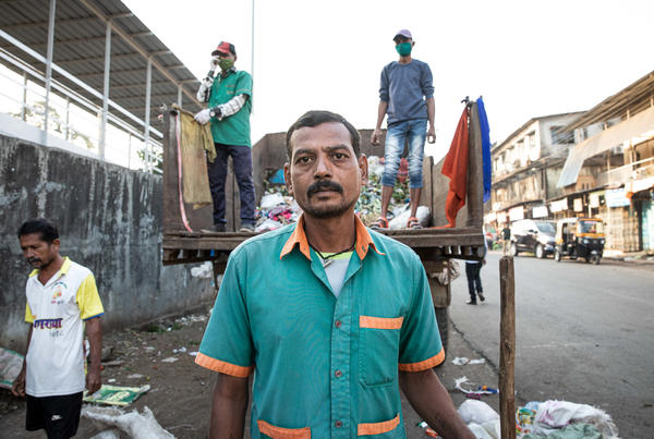 "Sanitation worker Ramesh Solanki cleans the streets outside Palghar railway station. ""I get up every morning at 5:30, and I see news about the vaccines on TV,"" he says. ""I don't know about any controversies. I just know I'm proud to be part of this."""