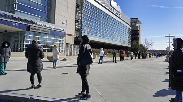 People wait in a socially distanced line to get their COVID-19 vaccinations at Gillette Stadium in Foxborough, Mass., last month. The NFL is making all 30 of its stadiums available to serve as mass vaccination sites.