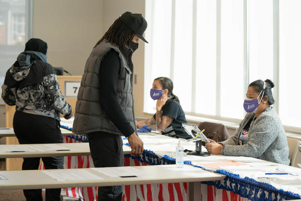 Poll workers help voters get ready to cast their ballots on Nov. 3 in Atlanta. State lawmakers are now considering legislation that could roll back some laws that made it easier for voters to cast ballots by mail.