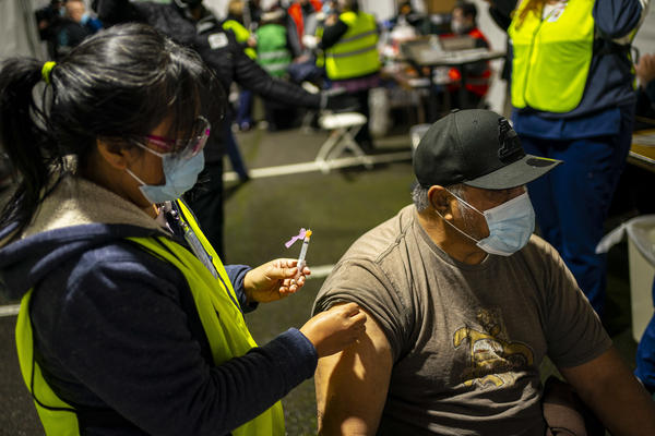 A person receives a COVID-19 shot in Federal Way, Wash., at a vaccination clinic for the Pacific Islander Community Association of Washington held on Feb. 4.