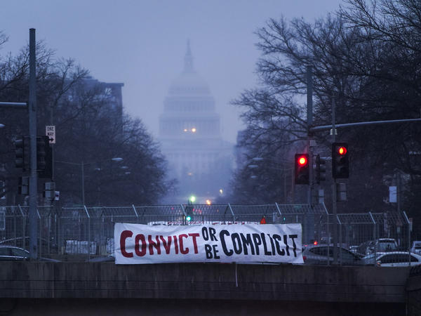 "A sign reading ""Convict or Be Complicit"" hangs from a bridge on North Capitol Street in Washington, D.C., on the second day of former President Donald Trump's second impeachment trial."