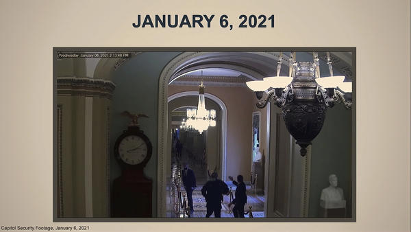 In this image from video, a security video shows U.S. Capitol Police Officer Eugene Goodman running past Sen. Mitt Romney, R-Utah (left), and urging him to turn around. Impeachment manager Stacey Plaskett showed the video as evidence the rioters came close to threatening lawmakers.