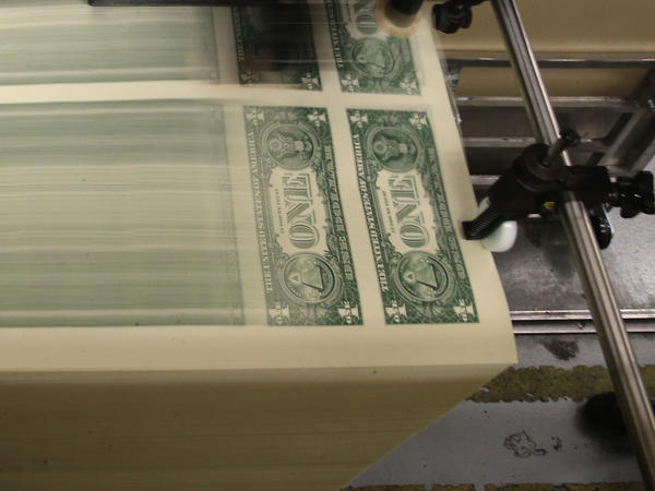 Sheets of one-dollar bills run through the printing press at the Bureau of Engraving and Printing in 2015 in Washington, D.C. Congressional forecasters projected the federal deficit this fiscal year will hit its highest since World War II.