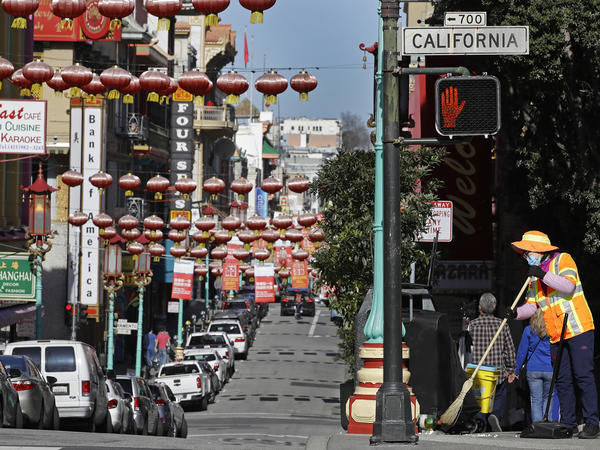 In this Jan. 31, 2020, file photo, a masked worker cleans a street in the Chinatown district in San Francisco. Police and volunteers have increased their street presence after a series of violent attacks against older Asian residents in Bay Area cities stoked fear and subdued the celebratory mood leading up to the Lunar New Year. (AP Photo/Ben Margot, File)