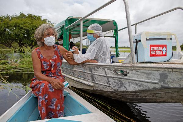 A health worker inoculates 72-year-old Olga D'arc Pimentel with a dose of Oxford-AstraZeneca's COVID-19 vaccine. She lives on the banks of the Rio Negro near Manaus, Brazil. A small study in South Africa has raised concerns about the AstraZeneca vaccine's effectiveness.
