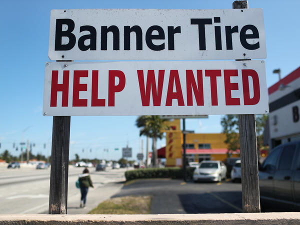 """A """"Help Wanted"""" sign is posted in front of a business on Feb. 4 in Miami. Although millions are unemployed, some businesses that require being on-site are struggling to find workers."""