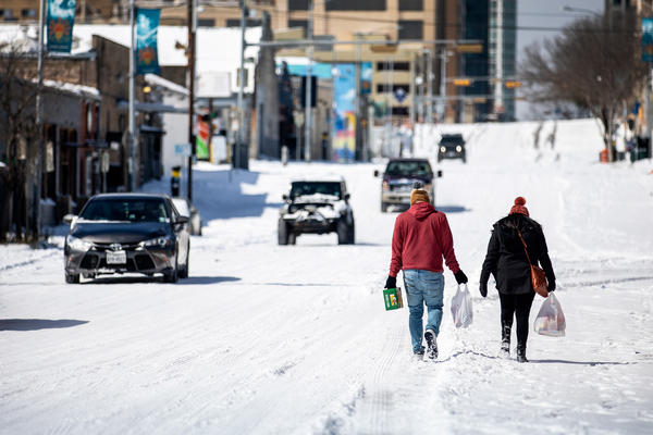 People carry groceries from a gas station on Monday in Austin, Texas. A winter storm has brought historic cold weather to the state, causing traffic delays and millions of customers to lose power.